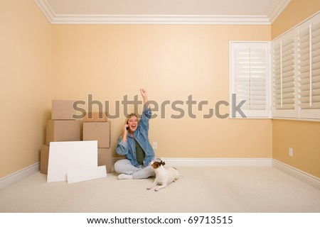 Pretty Woman on the Floor Using Phone Celebrating with Moving Boxes, Blank Signs and Dog in Empty Room.