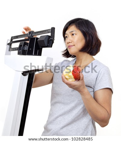 Pretty woman on weight scale eating an apple and looking concerned over recent weight gain as she weighs herself. - stock photo