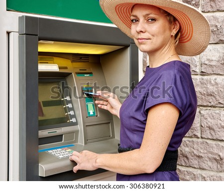 Pretty woman operates an ATM on the street