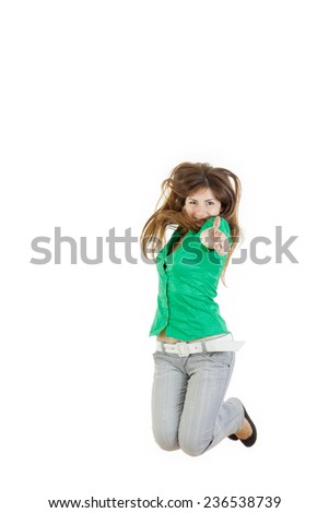 Pretty woman or girl jumping  with thumb up of joy excited isolated on white background in green shirt and gray jeans. Beautiful Caucasian model smiling.Photo of sure in success and belief in yourself - stock photo