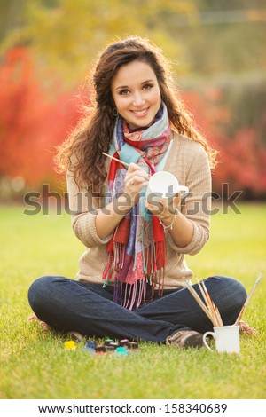 Pretty woman paints cups in the park - stock photo