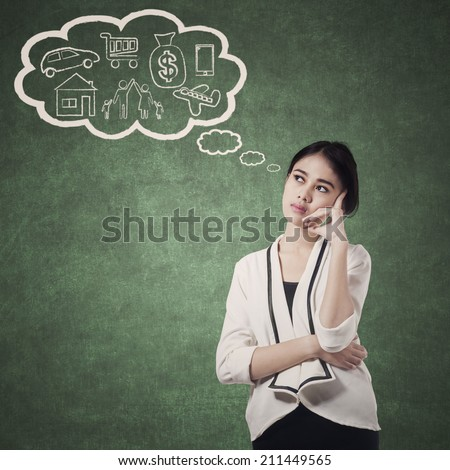 Pretty woman planning her future by thinking her plan - stock photo