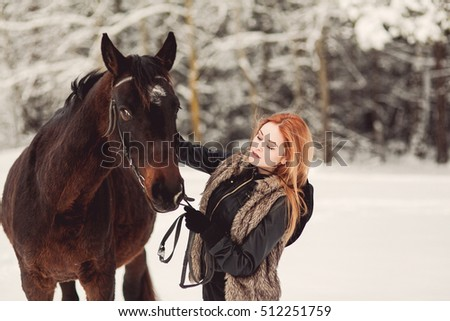 pretty woman posing on horse in winter park, ginger hair, nature, forest, hipster style, outdoor portrait