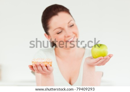 Pretty woman posing while holding a donut and a green apple against a white background