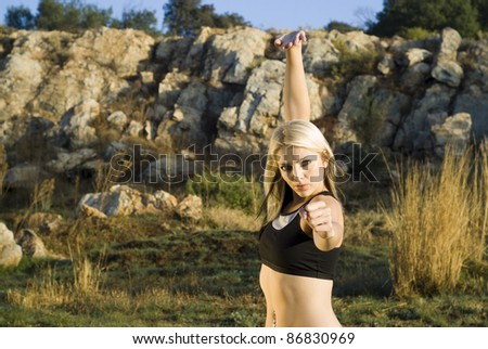 Pretty woman practicing exercise tai chi, kung fu in natural park close up - stock photo