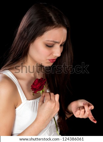 Pretty woman pricking her finger on a red rose