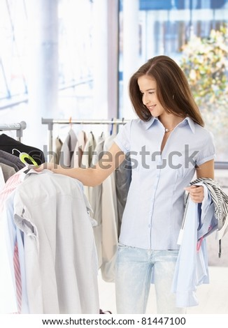 Pretty woman purchasing clothes in shop, smiling. - stock photo