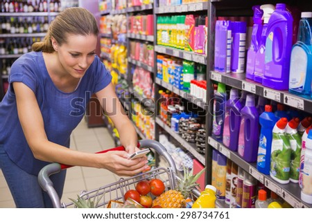 Pretty woman pushing trolley in aisle and texting at supermarket - stock photo