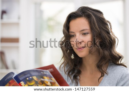 Pretty woman reading a magazine in her living room - stock photo