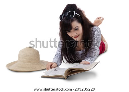 Pretty woman reading book while lying on the floor. isolated on white - stock photo