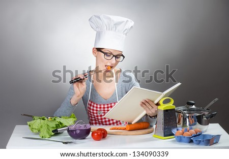 Pretty woman reading cooking with cookbook on grey background - stock photo