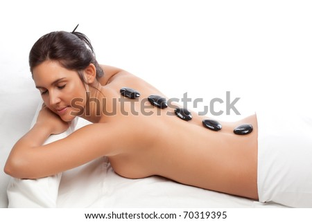 pretty woman receiving a therapy with hot stones in spa center over white - stock photo