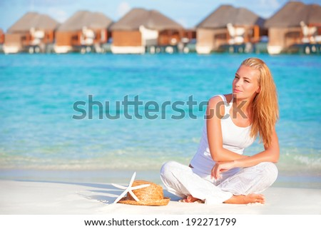 Pretty woman relaxation on the beach on tropical resort, luxury hotel on Maldives island, summer travel and vacation concept - stock photo