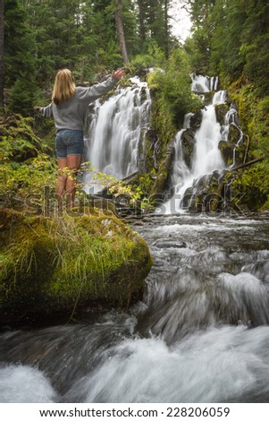 pretty woman relaxing and enjoying serene scene of national creek falls in Oregon - stock photo