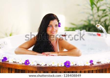 Pretty woman relaxing in jacuzzi of tropical hotel - stock photo