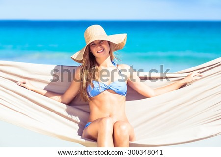 Pretty woman relaxing in the hammock and smiling at camera at the beach