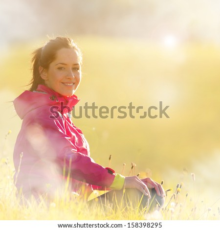 Pretty woman relaxing on a meadow during sunrise - stock photo