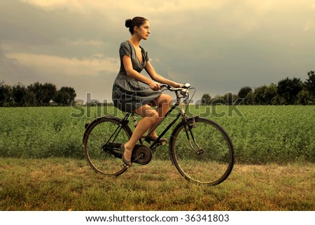 pretty woman riding bicycle in the countryside - stock photo