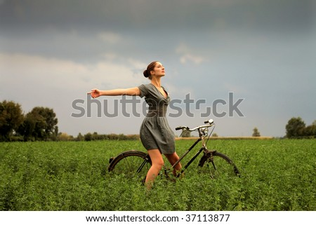 pretty woman riding bike in the nature - stock photo