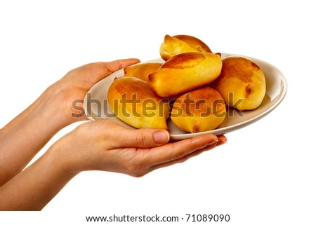 Pretty woman's hands holding a tasty pies on a plate isolated on  white background. - stock photo