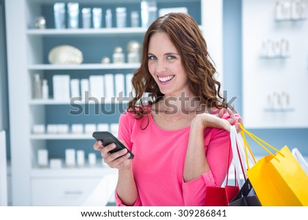 Pretty woman sending a text while shopping at the pharmacy