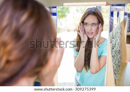 Pretty woman shopping for new glasses at the optometry store - stock photo