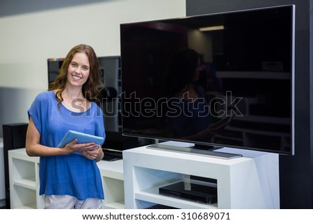 Pretty woman shopping for new television at the electronics store - stock photo