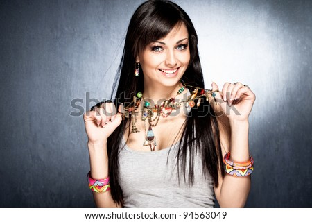 pretty woman show her colorful necklace with pendants - stock photo
