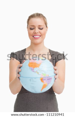 Pretty woman showing a globe against white background