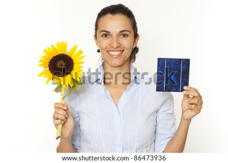 Pretty woman shows a solar cell and a sunflower