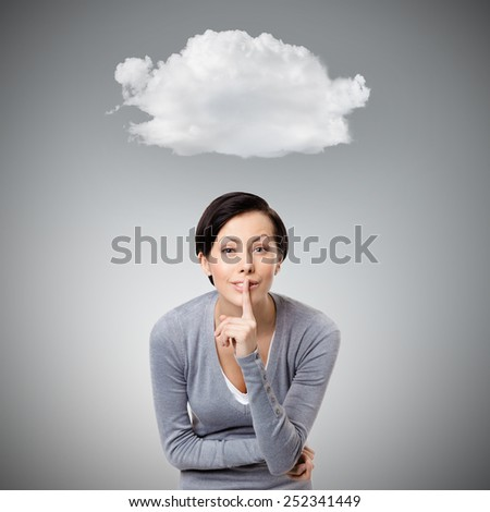 Pretty woman shows silence gesture touching her lips, isolated on grey background with cloud - stock photo