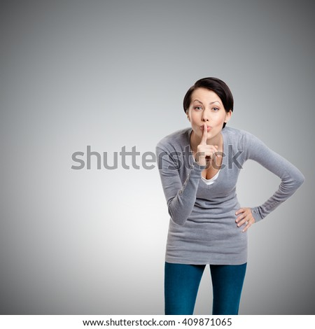 Pretty woman shows silence gesture with forefinger, isolated on grey background - stock photo