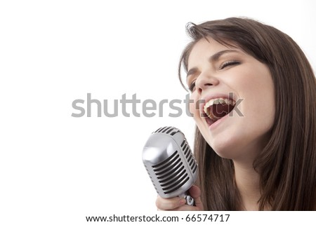 Pretty woman singing in microphone - stock photo