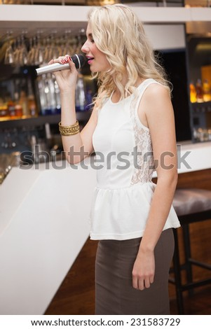 Pretty woman singing into a microphone with eyes closed at the nightclub - stock photo