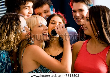 Pretty woman sings a song in the environment of her friends at a karaoke party