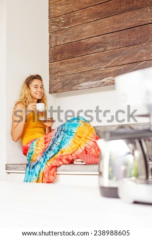 pretty woman sitting alone in a kitchen and drinking her morning coffee or tea