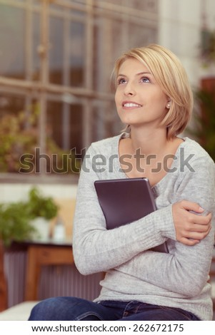 Pretty woman sitting daydreaming at home looking up into the air with a smile as she clasps her tablet-pc to her chest