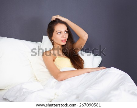 Pretty woman sitting in bed - stock photo