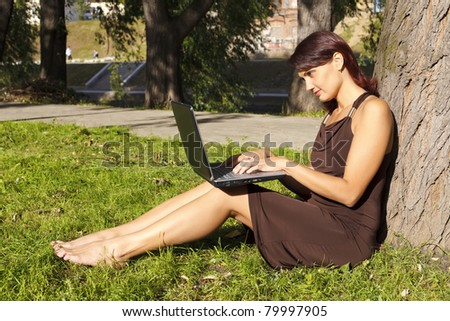Pretty woman sitting in park with a laptop