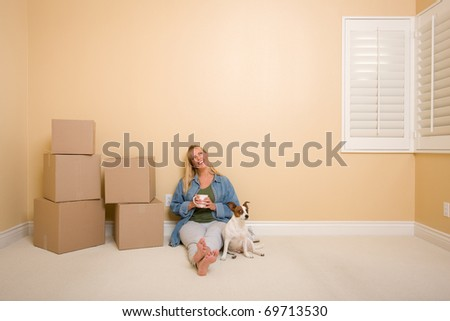 Pretty Woman Sitting on Floor with Cup Next to Moving Boxes and Dog in Empty Room. - stock photo