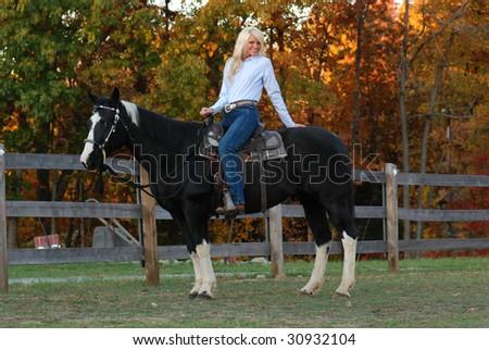 Pretty Woman Sitting on Horse - stock photo