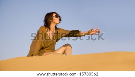 Pretty woman sitting on the dune - stock photo