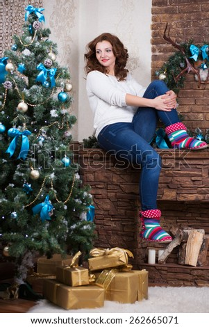 Pretty woman sitting on the fireplace near a fir-tree - stock photo