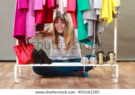 Pretty woman sitting on the floor under clothing from wardrobe. Young happy undecided shopper girl bought new clothes. Shopaholic concept. - stock photo