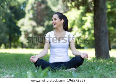 Pretty woman smile doing yoga exercises in the park- outdoor portrait of beautiful girl at park