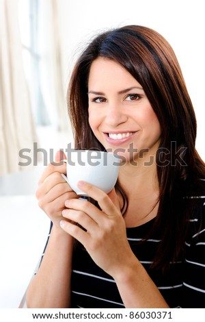 Pretty woman smiles while holding her cup of tea - stock photo