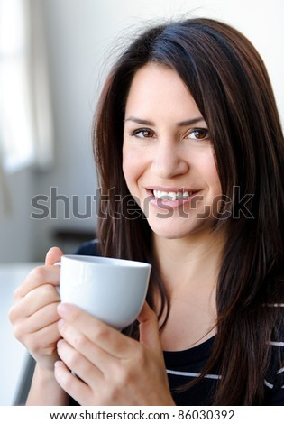 Pretty woman smiles while holding her cup of tea
