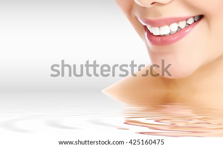 Pretty woman smiling against a grey background with copyspace