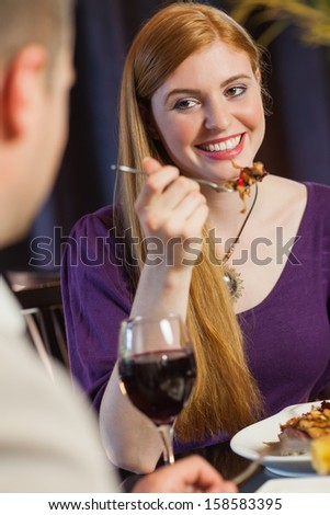 Pretty woman smiling at her husband during dinner in a classy restaurant - stock photo