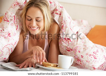 Pretty Woman Snuggled Under Duvet Eating Breakfast And Reading Newspaper - stock photo